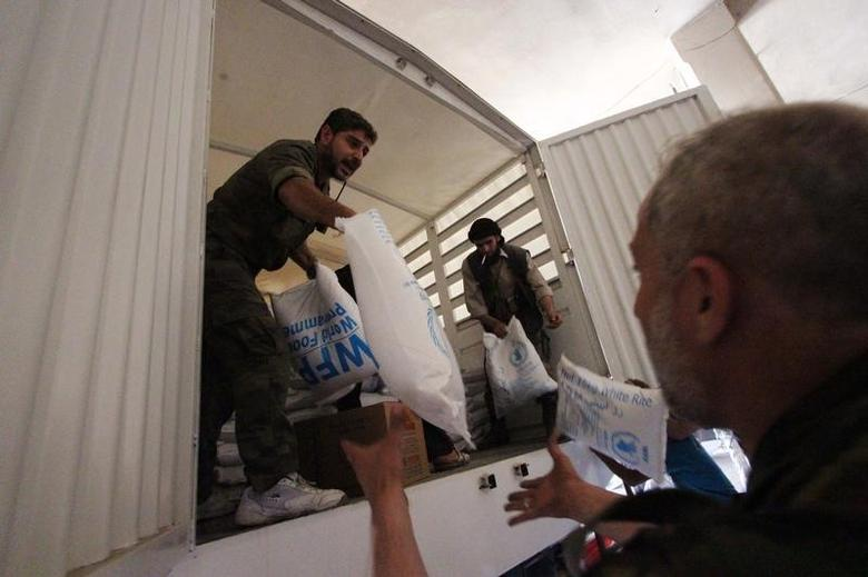 People unpack humanitarian aid inside a warehouse in Ghouta, eastern Damascus May 24, 2014. REUTERS/Badra Mamet