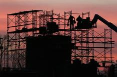 A construction crew erects scaffolding at sunset on a new housing project in Silver Spring, Maryland March 1, 2014.   REUTERS/Gary Cameron