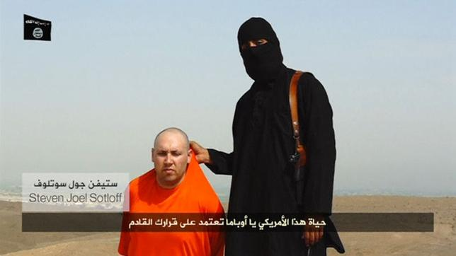 A masked Islamic State militant speaks next to a man purported to be U.S. journalist Steven Sotloff at an unknown location in this still image from an undated video posted on a social media website. REUTERS/Social Media Website via REUTERS TV