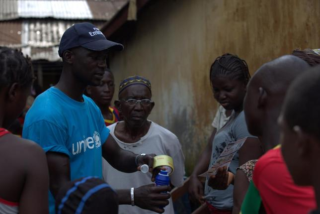A UNICEF worker shares information on Ebola and best practices to help prevent its spread with residents of the Matam neighborhood of Conakry, Guinea in this handout photo courtesy of UNICEF taken August 20, 2014. REUTERS/Timothy La Rose/UNICEF/Handout via Reuters