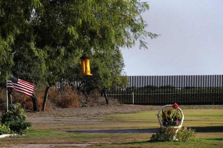 A U.S. flag blows in the wind in the backyard of a home facing the border fence at the United States-Mexico border outside of Brownsville, Texas, August 5, 2014.  REUTERS/Shannon Stapleton