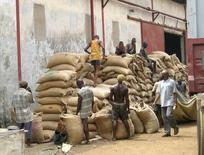 Nigerian workers load cocoa beans into shipping containers for export to Western markets, in Lagos, January 26, 2005. REUTERS/Thomas Ashby