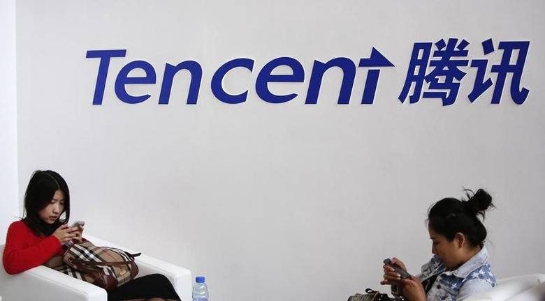 Visitors use their smarts phones underneath the logo of Tencent at the Global Mobile Internet Conference in Beijing May 6, 2014.  REUTERS/Kim Kyung-Hoon