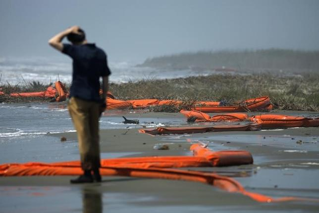 A television reporter stands beside oil booms at the coast of South Pass, south of Venice, Louisiana, as oil leaking from the Deepwater Horizon wellhead continues to spread in the Gulf of Mexico, May 2, 2010.  REUTERS/Carlos Barria