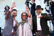 "Director Rakhshan Banietemad (C) and actors Habib Rezaei (R) and Peiman Moadi wave as they arrive at the red carpet for the movie ""Ghesseha (Tales)"" at the 71st Venice Film Festival August 28, 2014. REUTERS/Tony Gentile"