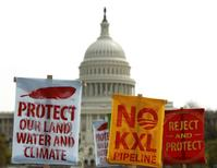 Members of the Cowboys and Indian Alliance, a group of ranchers, farmers and indigenous leaders, lift their signs in protest against the Keystone XL pipeline in front of the U.S. Capitol in Washington, in this April 22, 2014 file photo.  REUTERS/Gary Cameron/Files