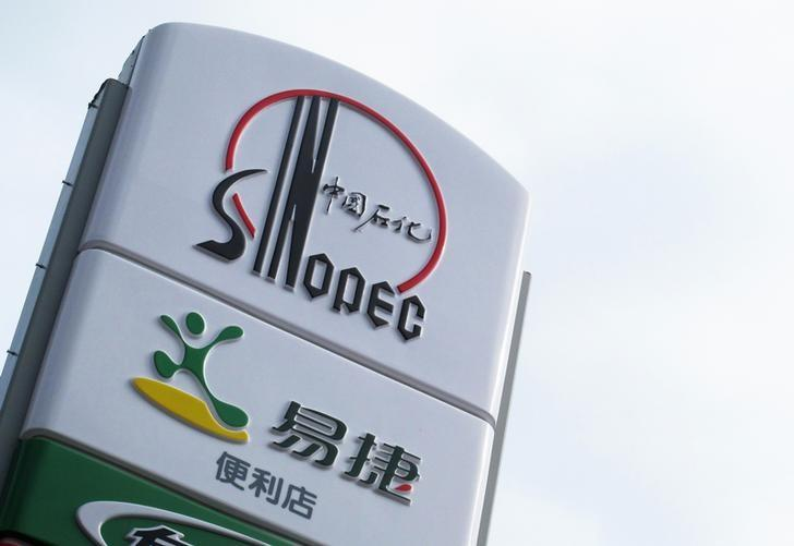 A Sinopec logo is seen on top of a logo of Easy Joy store at a gas station in Beijing, September 16, 2011. REUTERS/Sean Yong/Files