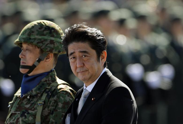 Japanese Prime Minister Shinzo Abe (R) reviews Japanese Self-Defence Forces' (SDF) troops during the annual SDF ceremony at Asaka Base in Asaka, near Tokyo, in this October 27, 2013 file photo. REUTERS/Issei Kato/Files