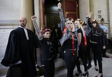 Activists of Ukrainian women's rights group Femen raise their fists as they enter the courtroom prior to a hearing over a topless demonstration they staged inside the Notre Dame cathedral, at Paris courthouse September 13, 2013. REUTERS/Jacky Naegelen