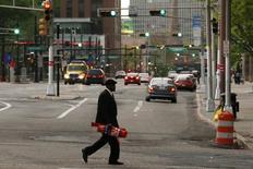 Un hombre cruza una calle en Newark, Nueva Jersey. Imagen de archivo, 13 mayo, 2014. El número de estadounidenses que solicitó por primera vez seguro por desempleo subió imprevistamente la semana pasada, pero eso probablemente no indique un cambio material en las condiciones del mercado laboral pues las peticiones siguen estando cerca de los niveles previos a la recesión. REUTERS/Eduardo Munoz