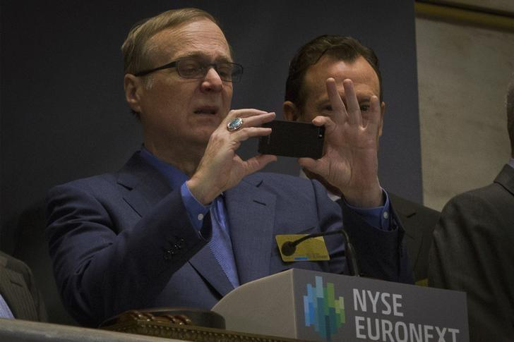 Seattle Seahawks owner and Microsoft co-founder Paul Allen takes a photo prior to ringing the opening bell at the New York Stock Exchange January 30, 2014.  REUTERS/Brendan McDermid/Files