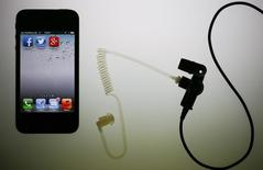 Application icons are displayed on an iPhone next to an earphone set in this illustration photo taken in Berlin, June 17, 2013.    REUTERS/Pawel Kopczynski