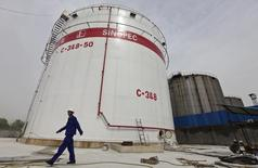An employee walks past oil tanks at a Sinopec refinery in Wuhan, Hubei province, April 25, 2012. REUTERS/Stringer