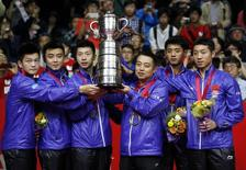 (From L to R) China's Fan Zhendong, Wang Hao, Ma Long, coach Liu Guoliang, Zhang Jike and Xu Xin pose with the world championships trophy on the podium during the medal ceremony after their men's final match victory over Germany at the World Team Table Tennis Championships in Tokyo May 5, 2014.   REUTERS/Toru Hanai