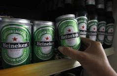 Imagen de archivo de una mujer que toma una lata de cerveza heineken en un restaurante en Bangkok. Julio, 2012. Las bolsas europeas abrieron el lunes a la baja luego de que unos decepcionantes datos de la producción industrial en China avivaron las preocupaciones sobre el ritmo de crecimiento de la segunda mayor economía del mundo. REUTERS/Sukree Sukplang