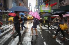 Personas cruzan una calle bajo la lluvia en Time Square, Nueva York, Imagen de archivo, 09 junio, 2014. Los precios al consumidor de Estados Unidos bajaron por primera vez en casi un año y medio en agosto, y la inflación subyacente se mantuvo contenida, lo que podría reducir la urgencia para que la Reserva Federal suba las tasas de interés. REUTERS/Carlo Allegri