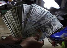 Un cajero cuenta dólares en una casa de cambios en Manila, ene 15 2014. El dólar subió el miércoles a un máximo de seis años frente al yen, mientras que el euro cayó desde niveles récord de cinco meses, después de que las proyecciones de la Reserva Federal mostraron un ritmo de alza de tasas más rápido durante los próximos años que lo inicialmente estimado en junio.         REUTERS/Romeo Ranoco