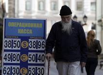 Мужчина у пункта обмена валют в Москве 16 сентября 2014 года. Рубль провел торги четверга в узком диапазоне, удержавшись от снижения благодаря поддержке экспортеров, которые могут сдержать ослабление и в пятницу, но уже на следующей неделе волатильность может снова усилиться, а тренд на ослабление - сохраниться. REUTERS/Sergei Karpukhin
