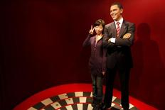 A visitor poses for a photo next to a wax statue of U.S. President Barack Obama at Madam Tussaud's wax museum in Shanghai January 21, 2009. REUTERS/Nir Elias
