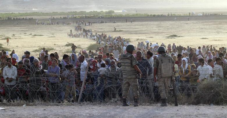 Turkish soldiers stand guard as Syrians wait behind the border fences near the southeastern town of Suruc in Sanliurfa province, September 18, 2014. REUTERS/Kadir Celikcan
