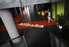 Un empleado pasa sobre un logo de Alibaba en sus oficinas en Hangzhou. Imagen de archivo, 20 junio, 2012. La gigante minorista china Alibaba tiene previsto vender unos 22.000 millones de dólares en acciones el jueves, coronando un proceso de dos semanas que generó un interés febril de inversores de todo el mundo y que podría convertirse en la mayor oferta pública inicial (OPI) de la historia. REUTERS/Carlos Barria