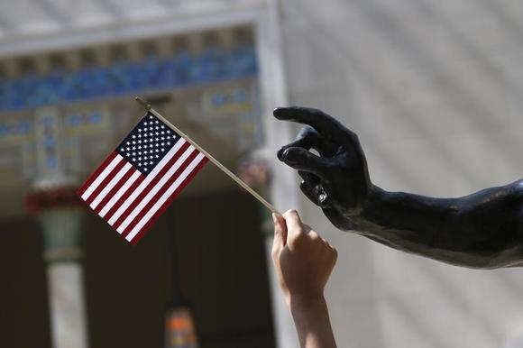 A girl holds a U.S. flag next to a sculpture after a naturalization ceremony in New York July 22, 2014. REUTERS/Shannon Stapleton