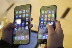 Un cliente sostiene unos teléfonos iPhone 6 y iPhone 6 Plus en una tienda de Apple en Manhattan, sep 19 2014. Holly Riggle, una oficinista de 29 años de Ohio, es el tipo de usuario que a Apple le encantaría tener para su nuevo iPhone 6, que sale a la venta este viernes.  REUTERS/Adrees Latif