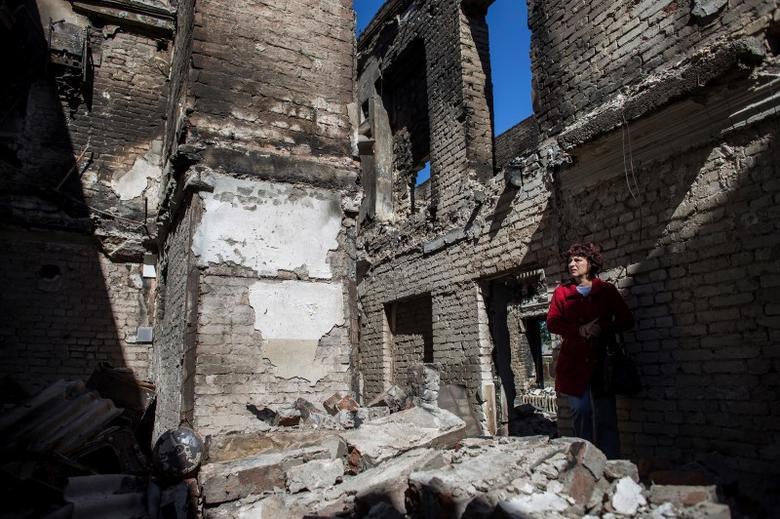 A woman stands inside her destroyed home in the town of Ilovaysk, eastern Ukraine, September 19, 2014. REUTERS/Marko Djurica