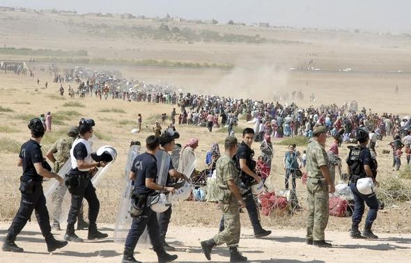 Turkish policemen and soldiers walk as Syrian Kurds wait behind the border fence to cross into Turkey near the southeastern town of Suruc in Sanliurfa province, September 19, 2014. REUTERS-Stringer