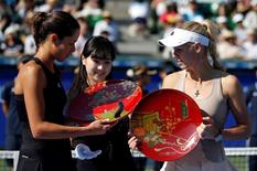 Ana Ivanovic (L) of Serbia and Caroline Wozniacki (R) of Denmark look at their trophies during an award ceremony after their Pan Pacific Open women's singles final tennis match in Tokyo September 21, 2014.   REUTERS/Toru Hanai