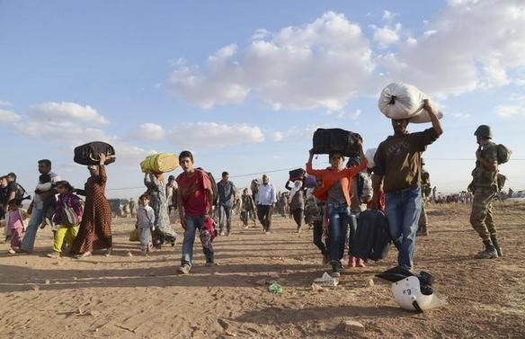 Syrian Kurds walk with their belongings after crossing into Turkey at the Turkish-Syrian border, near the southeastern town of Suruc in Sanliurfa province, September 20, 2014. REUTERS/Stringer