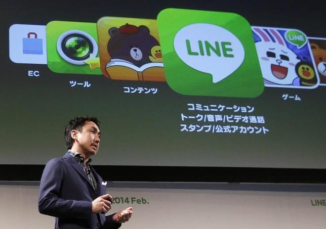 9月22日、韓国の検索サイト大手ネイバー日本子会社であるスマートフォン向け無料通信アプリ(応用ソフト)のLINEの年内の上場はないと明らかにした。写真はLINEのサービスを説明する出澤COO、2月撮影(2014年 ロイター/Yuya Shino)