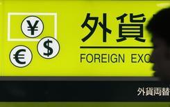Мужчина проходит мимо вывески пункта обмена валюты в аэропорту Ханэда в Токио 1 августа 2011 года. Курс доллара к корзине шести основных валют держится чуть ниже четырехлетнего максимума, а евро близок к 14-месячному минимуму. REUTERS/Yuriko Nakao