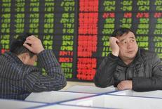 Инвесторы изучают котировки в брокерской фирме в Фуяне 21 февраля 2013 года. Азиатские фондовые рынки, кроме Китая, снизились во вторник под давлением местных компаний. Японский рынок закрыт по случаю государственного праздника. REUTERS/China Daily