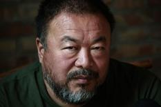 Dissedent Chinese artist Ai Weiwei reacts during a group interview at his studio in Beijing May 22, 2013. REUTERS/Petar Kujundzic