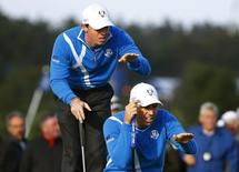 European Ryder Cup players Sergio Garcia (R) and Rory McIlroy line up a putt on the eighth green during their foursomes 40th Ryder Cup match at Gleneagles in Scotland September 26, 2014.  REUTERS/Eddie Keogh