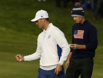 European Ryder Cup player Martin Kaymer (L) celebrates as he stands with U.S. Ryder Cup player Jordan Speith on the seventh green during their fourballs 40th Ryder Cup match at Gleneagles in Scotland September 27, 2014.      REUTERS/Phil Noble