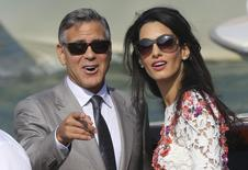 U.S. actor George Clooney and his wife Amal Alamuddin stand on a water taxi on the Grand Canal in Venice September 28, 2014. REUTERS/Stefano Rellandini