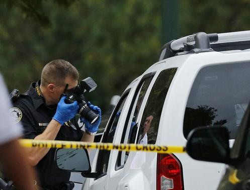A crime technician photographs evidence in front of the Ethiopian Embassy in Washington September 29, 2014. REUTERS-Gary Cameron