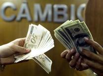 Um brasileiro troca dólares por reais em corretora de câmbio no Rio de Janeiro. 04/08/2003 REUTERS/Bruno Domingos REUTERS