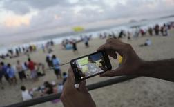 Torcedor assiste a uma partida da Copa do Mundo de 2014 pelo celular, em Copacabana, no Rio de Janeiro. 12/07/2014.   REUTERS/Nacho Doce