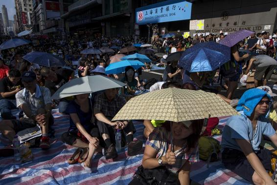 Protesters sit under umbrellas at a main street at Mongkok shopping district after thousand of protesters blocked the road in Hong Kong October 1, 2014.  REUTERS/Tyrone Siu