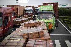 Camiones cargados con cobre en la zona de ingreso a la zona franca de Shanghái en Shanghái, sep 24 2014. Los precios del cobre repuntaron levemente desde mínimos de tres meses y medio el miércoles pero se mantuvieron vulnerables a la fortaleza del dólar, las preocupaciones por la escasa demanda del mayor consumidor mundial, China, y el descontento en Hong Kong. REUTERS/Carlos Barria