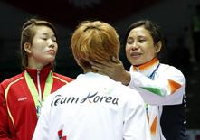 India's bronze medallist Laishram Sarita Devi (R) talks with South Korea's silver medallist Park Ji-na during the medal ceremony for the women's light (57-60kg) boxing competition at the Seonhak Gymnasium during the 2014 Asian Games in Incheon October 1, 2014. REUTERS/Kim Kyung-Hoon