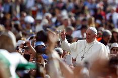 Pope Francis waves as he arrives to lead his weekly general audience in Saint Peter's Square at the Vatican October 1, 2014. REUTERS/Tony Gentile