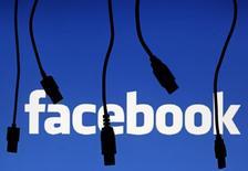 La silueta de cables electrónicos frente al logo de Facebok en Saravejo. Imagen de archivo, 25 septiembre, 2014. Las autoridades regulatorias de la Unión Europea aprobaron el viernes la oferta de 19.000 millones de dólares de Facebook, la red social más popular del mundo, por la empresa de mensajes en móviles WhatsApp. REUTERS/Dado Ruvic