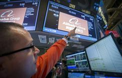 "Specialist Trader Neil Gallagher points to the ticker symbol for Alibaba Group Holding Ltd during the company's initial public offering (IPO) under the ticker ""BABA"" at the New York Stock Exchange in New York September 19, 2014. REUTERS/Brendan McDermid"