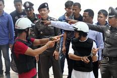 Подозреваемые в убийстве британских туристов рабочие из Мьянмы (в шлемах) на следственных мероприятиях на острове Тау 3 октября 2014 года. Двое рабочих из Мьянмы сознались в убийстве британской пары на популярном курорте в Таиланде, что подтвердил проведенный ДНК-тест, сообщила полиция королевства в пятницу. REUTERS/Stringer