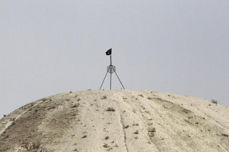 A fluttering Islamic State flag, is flown over a hill in Tel Abyad town on the Syrian-Turkish border, Raqqa countryside September 24, 2014. REUTERS/Stringer/Files