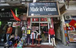 Vendors sit outside a shop selling clothes in Hanoi October 3, 2014. REUTERS/Kham